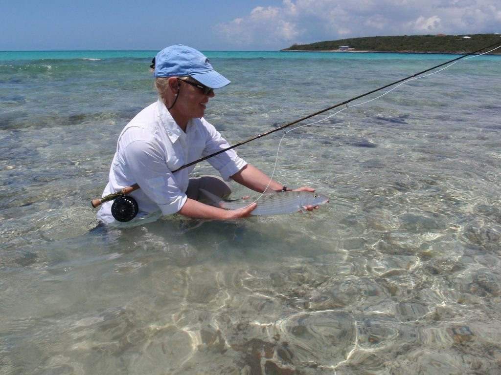 A woman standing waist-deep in clear turquoise water holding her fishing rod and her catch (bonefish)